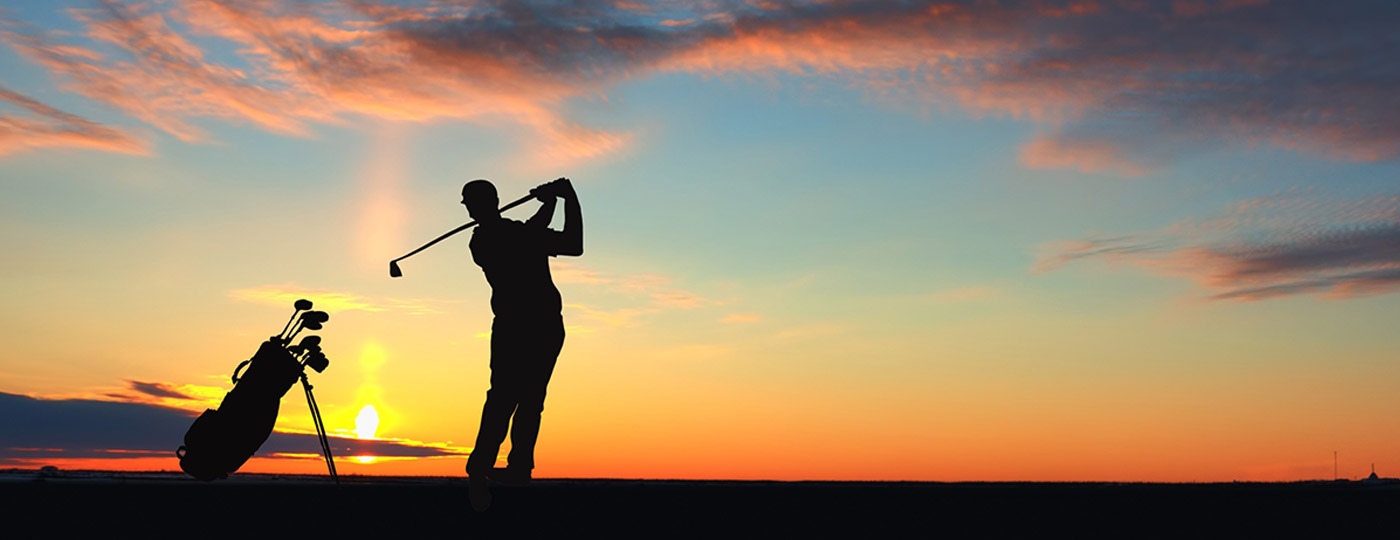 Man playing golf in the sunset